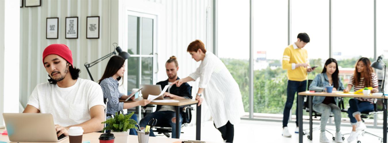 Büro mit unterschiedlichen Tischen und Personen, die arbeiten