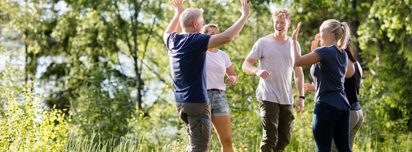 Gruppe von fünf Personen draussen beim Outdoor-Teambuilding
