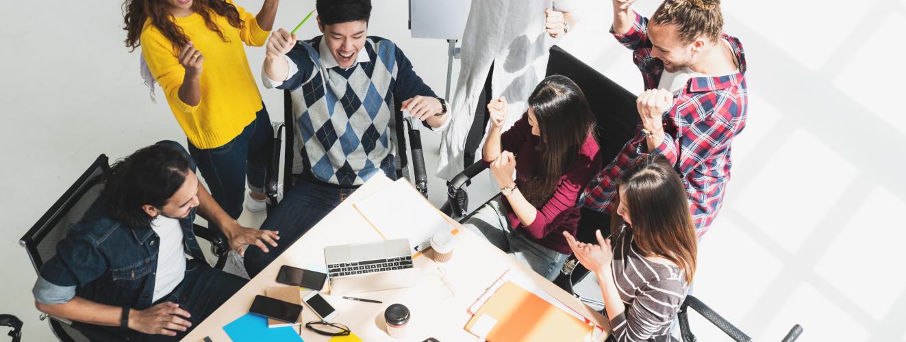 Sieben Personen um Tisch herum gruppiert beim Teamentwicklungs-Training